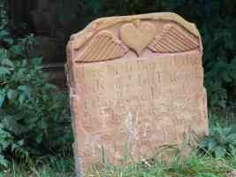 red gravestone with winged heart emblem
