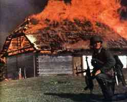 soldier with MP 40 in front of burning building in russia