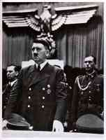 hitler standing in court in front of large eagle crest