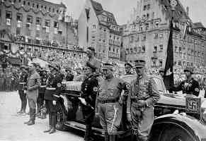 hitler stands in a touring car in a german public square
