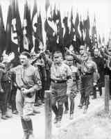 hitler walking and heiling in front of nazi flags