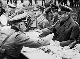 stuffed dummy of hitler sits down for lunch