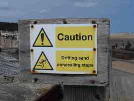 caution drifting sand concealing steps