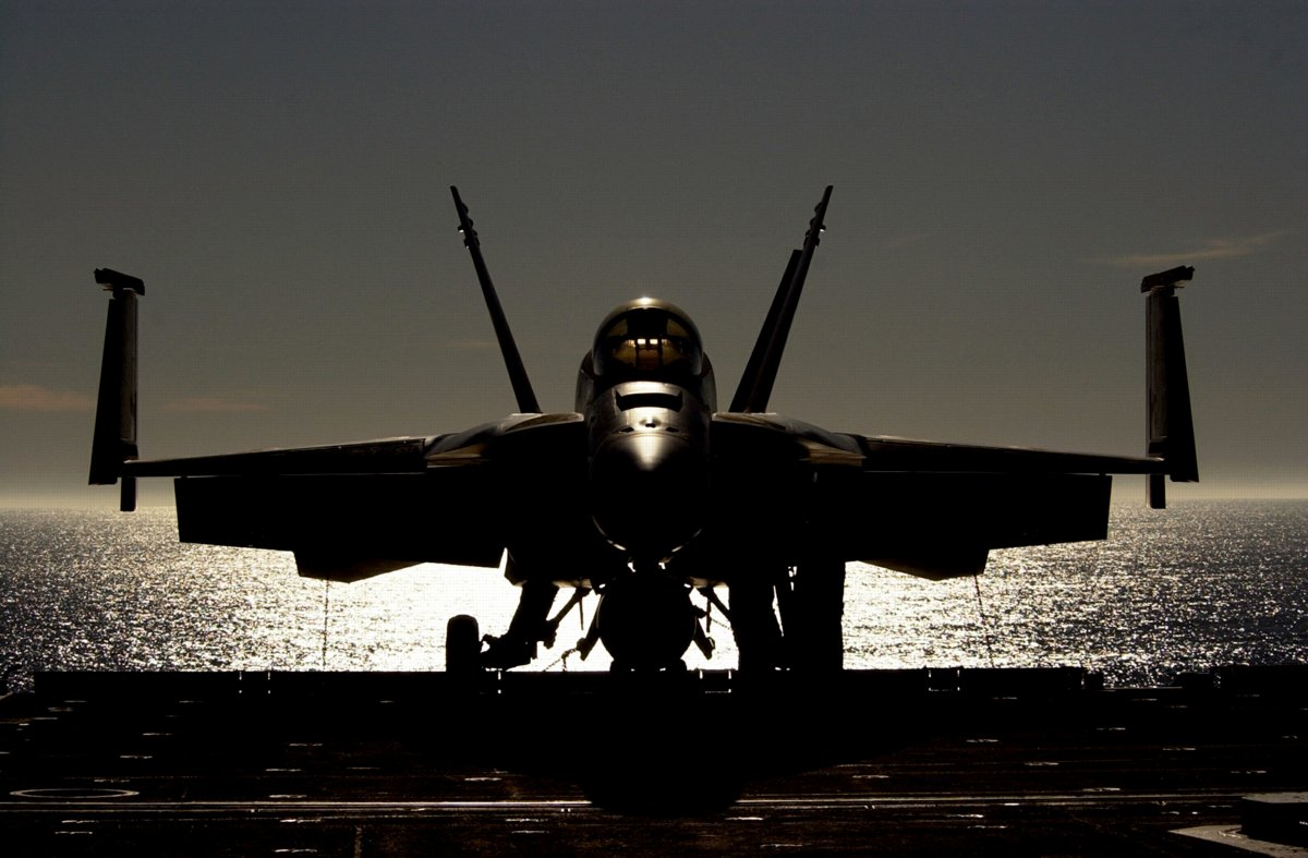 Jet Fighter Waiting On Airecraft Carrier At Dusk